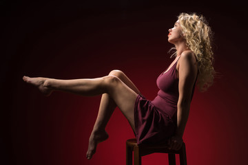 Beautiful woman with blonde long curly hair. Beauty portrait of modern fashion, red background. © Artenex
