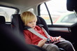 Portrait of a bored little boy sitting in a car seat. Safety of children.