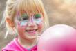 Leinwanddruck Bild - glückliches geschminktes Mädchen beim Kinderkarneval auf einem Freizeitpark mit einem Luftballon