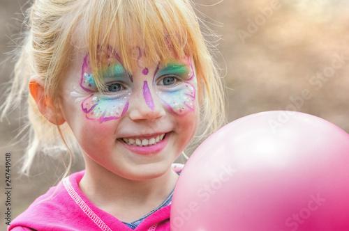 Leinwandbild Motiv glückliches geschminktes Mädchen beim Kinderkarneval auf einem Freizeitpark mit einem Luftballon