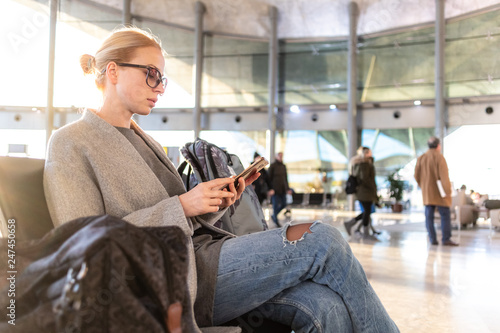Foto Murales Casual blond young woman using her cell phone while waiting to board a plane at the departure gates at the airport terminal.