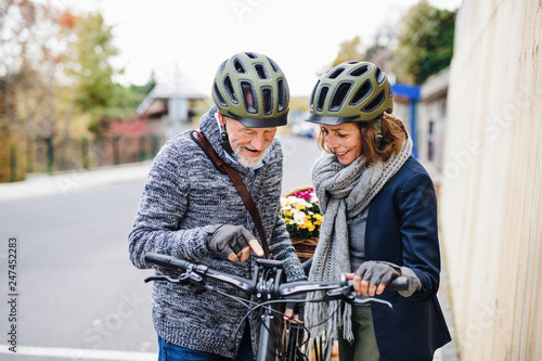 Active senior couple with electrobikes standing outdoors on pathway in town. - 247452283