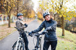 Leinwandbild Motiv Active senior couple with electrobikes standing outdoors on a road in nature.