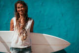 happy surfer girl with surfboard in front of blue wall