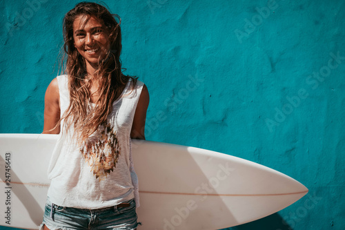 Leinwandbild Motiv happy surfer girl with surfboard in front of blue wall