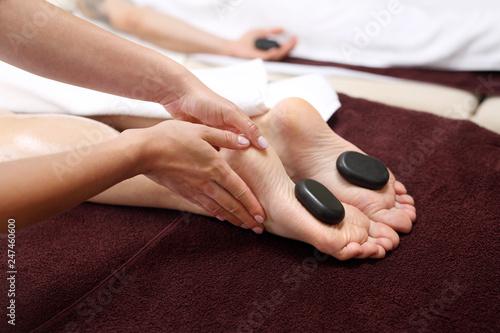 Masaż gorącymi kamieniami.  Kobiece stopy z kamieniami bazaltowymi, relaks w salonie spa. - 247460600