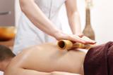 Masaż bambusowy. Relaksacyjny masaż bambusem. Masażysta masuje ciało przy użyciu bambusowych kijów.