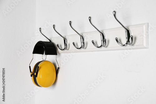 Leinwanddruck Bild Protective headphones hanging on white wall. Safety equipment