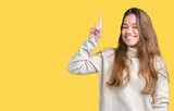 Young beautiful brunette woman wearing turtleneck sweater over isolated background pointing finger up with successful idea. Exited and happy. Number one.