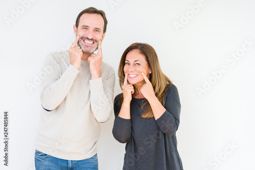 Leinwandbild Motiv Beautiful middle age couple in love over isolated background Smiling with open mouth, fingers pointing and forcing cheerful smile