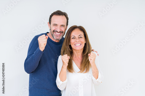 Leinwandbild Motiv Beautiful middle age couple in love over isolated background excited for success with arms raised celebrating victory smiling. Winner concept.