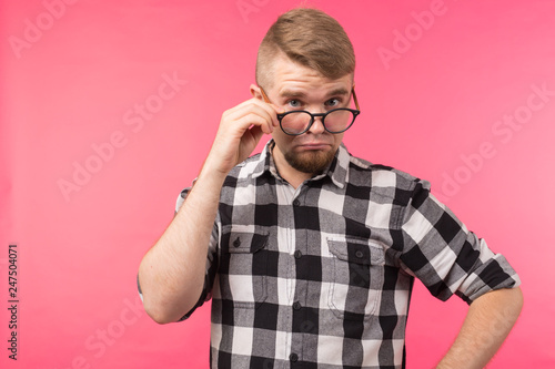 Surprised man in a plaid shirt takes off his glasses on pink background - 247504071