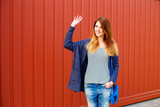 Cheerful young red-haired girl stands in the street near the house with red gate and waving to friends or neighbours. - 247515083