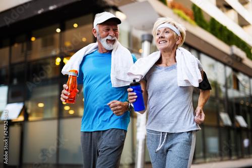 Leinwandbild Motiv Healthy senior, couple jogging in the city at early morning with sunrise