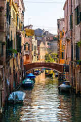 VENICE / ITALY - OCTOBER 11, 2010: Citycsape of water duct and gondola, colorful narrow venetian street and canale, best place for romantic trip