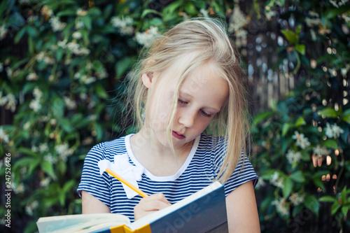 Leinwandbild Motiv Girl child with notebook outdoors portrait. Girl writing