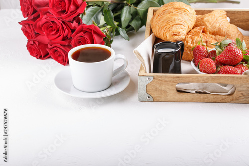 Leinwandbild Motiv Cup of coffee and croissant on wooden tray. Festive breakfast with a bouquet of red roses on white table. Copy space.