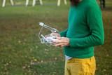 Man piloting drone with remote control in public playground, Zagreb, Croatia.