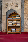 11/18/2018 Cairo, Egypt, shelf with religious books in Arabic in the middle of a great mosque with carpets