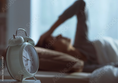 Leinwanddruck Bild Woman waking up in the morning and alarm clock