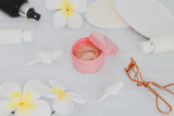 spa inspired set of scrub body lotions and spray with make-up details such as lash curler and lipgloss with flowers and seashells on light colored wood