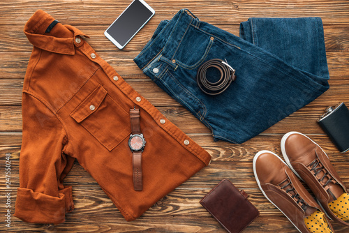 Flat lay with clothes, smartphone and wallet on wooden background
