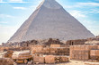 View of the incredibly majestic pyramid of the cheops on a sunny day in the desert with ancient ruins in the foreground