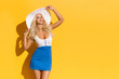Sexy Blond Woman In Mini Dress And White Sun Hat Is Looking Away