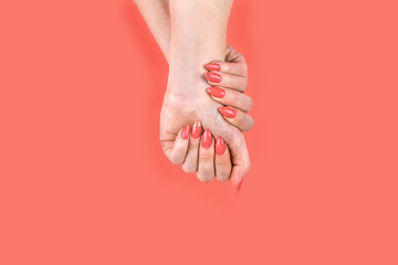 Young woman's hand with perfect Coral manicure.