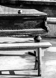 Old piano with bench in foreground.