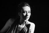portrait of  young woman in elegant dress studio dark background bw - 247584299