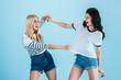 Leinwandbild Motiv Irritated young women fighting on blue background