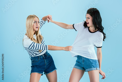 Irritated young women fighting on blue background - 247592290