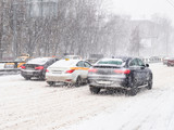 cars drive at snow-covered urban road in snowstorm