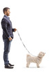 Young man standing with a maltese poodle dog