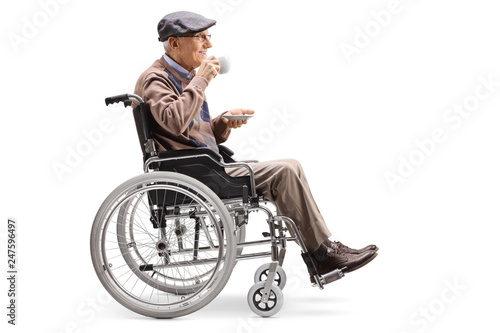 Leinwandbild Motiv Elderly man in a wheelchair drinking a cup of coffee