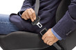 Male hands fastening a car seat belt for road safety