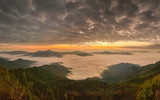 sunrise at Doi Pha Tang, beautiful mountain view morning panorama 180 degree of top hill around with sea of mist with yellow sun light and cloudy sky background, Chiang Rai, Thailand.