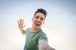 Man taking a selfie on a blue sky background