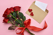 True love. Envelope with paper note, bouquet of roses with red ribbon