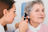 doctor examining elderly patient ear , using otoscope, in doctors office. Senior woman getting medical ear exam at clinic. - 247617484