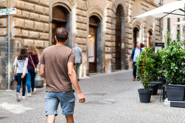 Orvieto, Italy Italian outdoor street in Umbria historic city town village cobblestone road alley with people tourists young man back walking in summer