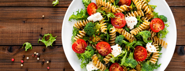 Italian pasta salad with wholegrain fusilli, fresh tomato, cheese, lettuce and broccoli on wooden rustic background. Mediterranean cuisine. Cooking lunch. Healthy diet food. Top view. Banner © Sea Wave