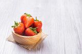 Fresh strawberries in a bowl on wooden table .