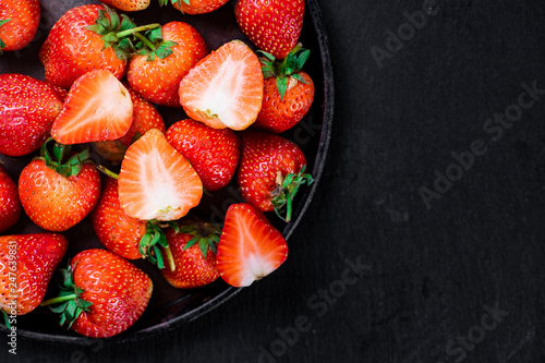 Foto Murales Fresh strawberry in wrought plate on  dark board.