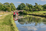 A canal barge moored next to the tow path, near a bridge. Reflections in the water. - 247641238