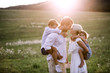 Young family with small children in summer nature at sunset. - 247655070