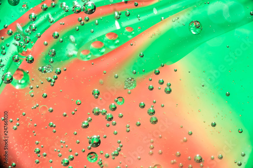 Leinwandbild Motiv oil bubbles in water close up on a red green background