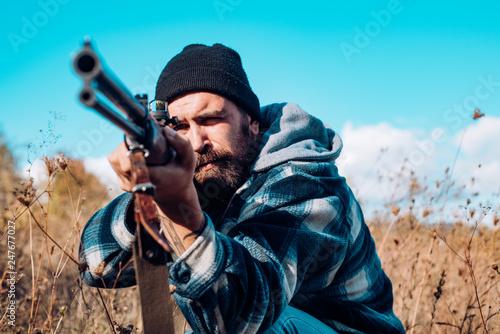 Leinwandbild Motiv Hunting in America. Hunter with shotgun gun on hunt. Hunter aiming rifle in forest. Hunter man. Hunting period, season. Male with a gun.