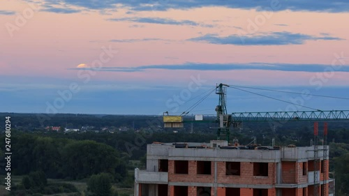 Full Moon a couple of hours before an eclipse rising over a construction site in Warsaw Poland, clip with camera motion